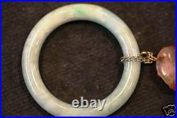 Estate Chinese baby bangle with one suspending a chalcedony carving. 20 Century